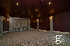 Gray faux painted media center and columns in a media room with leopard print carpet.  www.facebook.com/mcthegarage