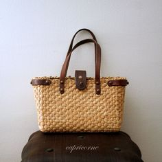 John Romaine wicker 60's.  I had a leather purse for Fall and Winter and a wicker purse for summer.