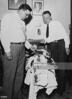 Police officers examining the bloodstained clothing of outlaw John Dillinger, on the day he was shot and killed by police and federal agents in Chicago, 22nd July 1934.