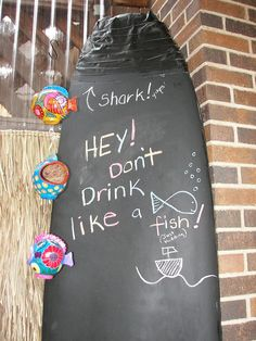 An old surfboard painted with chalkboard paint stands in the tiki bar. Pool Ideas, Bar Ideas, Surfboard Painting, Treehouse Ideas, Tiki Bar Decor, Backyard Renovations, Tiki Lounge, Tiki Bars, Backyard Bar
