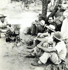 Entre vaqueiros, o doutor Guimarães Rosa aguarda a comida ficar pronta: feijão, arroz, farinha e carne seca, incrementada por um pouco de pimenta