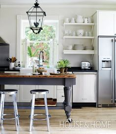 In the kitchen, temper the look of metal seating and tables on casters with clean-lined cabinetry and traditional lighting, like designer Margot Austin did in this well-balanced space. | Photographer: Donna Griffith