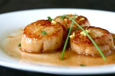Caramelized Seared Scallops - with correct link  12 large sea scallops  Pinch of kosher salt  Freshly ground black pepper  4 tablespoons clarified butter  ½ cup white sugar, spread on a flat plate  ½ cup dry white wine  Juice of one lemon, freshly squeezed  1 tbsp. finely chopped flat parsley  8 chives  1 tbsp. lemon zest
