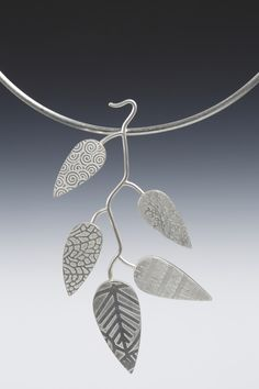 Five Sterling leaf shaped hollow forms on a sterling neck wire.