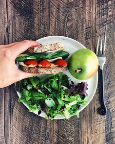 turkey and cheese on whole wheat with hummus, spinach, onion and tomato, a side of mixed greens and a pear.