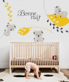 """Three light grey koala wall decals with black and yellow leaf decals of various sizes and a """"boone nuit"""" wall quote written in script in dark grey on a white wall above a wooden crib in a child's nursery."""