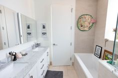 A light, bright, and airy bathroom features circular statement artwork.