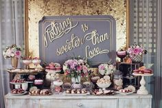 Glamorous gold and gray wedding dessert display - decked with flowers and that adorable backdrop