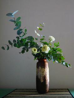 Ikebana nella penombra. By Jenny Favari Il bianco acerbo dei ranuncoli fa capolino tra profumati rami di eucalipto e diffonde una fresca luce nella penombra del mio studio. (Studio Spazio Bianco)