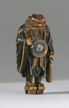 """WOOD NETSUKE 19th Century In the form of the oni Nembutsu holding a hammer and account book with a gong hanging from his neck and an umbrella slung over his back. Unsigned. Height 1.75"""" (4.4 cm). See N & I.A. Lazarnick, Vol. 2, page 1295 for nearly identical example."""