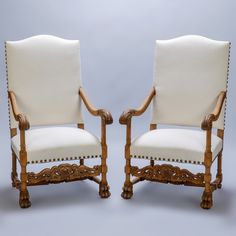 "Pair French Highly Carved and Bleached Throne Chairs  --  Late 19th century pair of large, French, throne style chairs in bleached oak. Beautifully detailed: foliate carving on the arms and apron, lion paw feet and turned side stretchers. Newly covered in muslin with decorative brass nails and ready for the fabric of your choice. Arm height is 25-1/2"" - 30"". Seats are 18"" high and 19"" deep.  --   Item:  7018  --  Retail Price:  $3895"