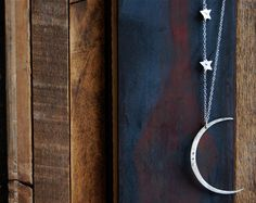 A silvery crescent moon, suspended from a chain with two stars. $79.00, from SoulPeaces.