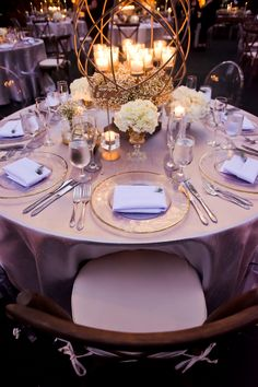 Al Fresco Black-Tie Glamour | Miami + Fort Lauderdale, FL | silver satin table cloth with wood cross back vineyard chair and globe centerpiece with glass chargers and white napkin