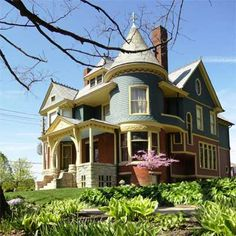 Restored and Highlighted - Sunny yellow trim outlines a colorful Queen Anne backdrop for a vibrant garden.