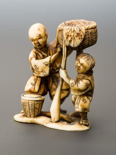 MAN WITH BOY AND BASKETS Netsuke, ivory. Japan, Meiji period or later