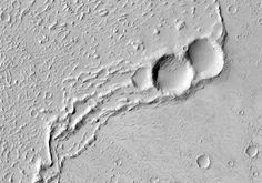 Lava Flows in Daedalia Planum To the southwest of Arsia Mons in Daedalia Planum, wide lava flow units emanating from the volcano coalesce to...