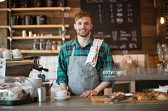 Stock Photo : Happy barista standing at cafe counter