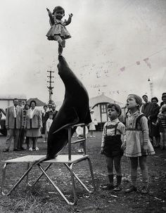 A seal puts on a show by balancing a doll before young viewers at a performance of the Krone Circus in Aachen, Germany, 1961//