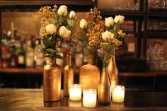 Create your own statement centerpiece for your party by repurposing glass bottles with a coat of gold paint.