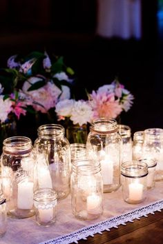 table full of candles in jars/holders of varying sizes/types