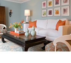 Living room in pale aqua and white, with orange accents.