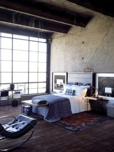 Concrete and Industrial Bedroom, made warm with textured Linens, Furnishings, and Art.