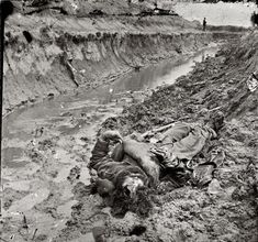 "April 3, 1865. Petersburg, Virginia. ""Dead Confederate soldier in trenches of Fort Mahone."""