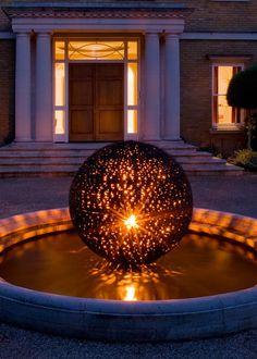 beleuchtete Gartenkugel bei Nacht in einem englischen Garten