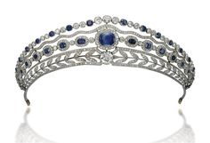 A Belle Epoque Sapphire and Diamond Tiara The base designed as an openwork wreath of diamond-set laurel leaves, centering upon a circular-cut diamond collet, surmounted by a series of graduated cushion-shaped sapphires in diamond-set clusters, a diamond-set wavy line and alternated diamond and sapphire collets on top, 1910s