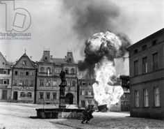 Two anti-tank Infantrymen of the 101st Infantry Regiment, dash past a blazing German gasoline trailer in the square of Kronach, Germany, 14th April, 1945