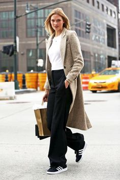 Le Fashion Blog Model Off Duty Karlie Kloss Fall Winter Style Tweed Textured Tan Coat Cropped Sweater Wide Leg Pants Adidas Gazelle Sneakers
