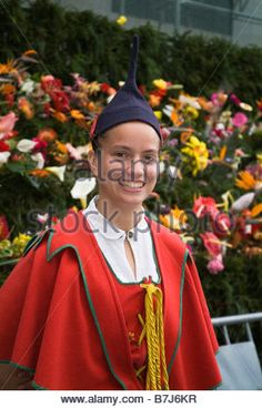 Flower Festival FUNCHAL MADEIRA Girl in traditional costume in front of Wall of Hope flower display - Stock Photo