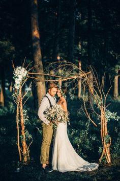 Жених и невеста у свадебной арки с букетом цветов