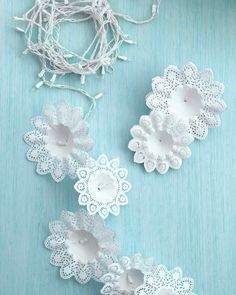 """To make one of these garlands, slide a store-bought paper bouquet holder over each bulb. Hang the """"snowflakes"""" inside a doorway or a window, and then plug in the lights."""