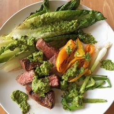 Grilled steak with a avocado chimmichurri sauce over grilled romaine, peppers and green onions.   Just grill everything. Romaine on the grill is amazing! Seriously you must try it.   The Avocado Chimmichurri sauce is adapted from a Heather Christo recipe.  Half a cup of olive oil, cup of flat leaf parsley, half a cup of mint, 3 cloves of garlic, juice and zest of two lemons, salt and pepper to taste - food processor that- toss in pistachios and half a avocado.