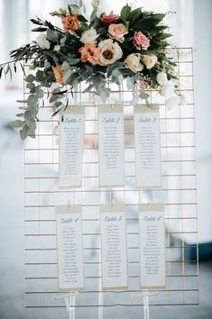 Gold wire mesh reception table seating chart with pink and peach flowers and greenery   Bird on the Wall Photography