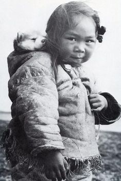 An Inuk girl with her husky puppy in the hood of her amatiuq circa 1920. Mothers would also carry their infants in the same manner. This little girl is playing mommy and baby with her puppy.
