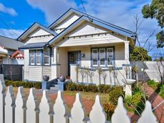 Photo of a weatherboard californian bungalow house exterior with picket fence & hedging - House Facade photo 523029. Browse hundreds of images of californian bungalow house exteriors & photos of weatherboard in facade designs.