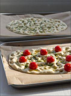 frisch gebackenes Focaccia mit Rosmarin und Meersalz und Tomaten und Kräutern