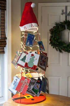 DIY Christmas Lights Idea! Create a Christmas card holder using a tomato cage, decorative clips and a string of LED mini lights. You can get creative and add a Santa hat or dress it up like Frosty the Snowman!