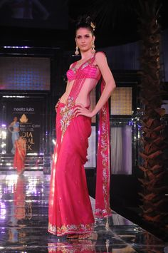 Hot pink draped saree with gold and silver  embellishments and a hot pink blouse.