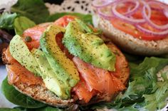 Whole wheat bagel thin with lox, avocado, tomato, onion, and fresh cracked pepper on a plate of arugula