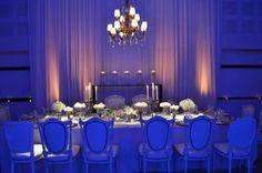 Mesa principal para los novios y sus familias: sillas de estilo Luis XV blancas para todos los invitados, distintas flores blancas sobre la mesa, araña de bronce de 12 luces, y detrás un dressoir con cilindros de agua con pétalos y velas flotantes.