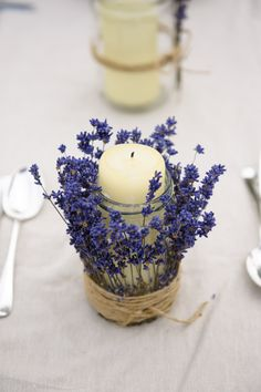 A home made centre piece using a jar, a pillar candle, some brown string and a bunch of lavender, perfect for a Spring wedding!