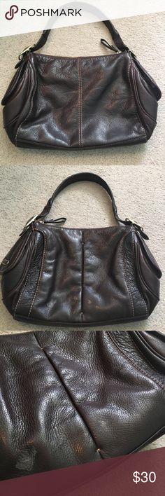 Tumi Bag Brownish purple colored leather bag. Shows wear on front and back as pictured. Strap has a heavy crease as shown (both sides). Interior in good shape. Tumi Bags