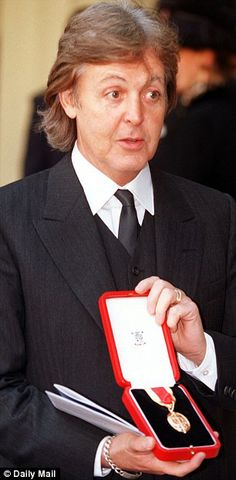 """Mar 11 1997, Paul McCartney was knighted by Queen Elizabeth II for his """"services to music."""" Here, Sir Paul shows his medal for knighthood."""