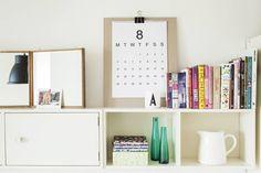 Kalenterin ja kasan kortteja Sareda tilasi RK-Designin nettikaupasta. Kalenteri on kiinnitetty nipsulla pahviin. Olkkarista löytynyt A-muki on Arne Jacobsenin suunnittelema. Värikkäät vihkoset avohyllyllä ovat ranskalaisen Laduréen reseptikirjasia. Niiden vieressä on Ikean lasipulloja ja valkoinen maitokannu, jonka Sareda nappasi äidin astiakaapista.
