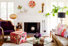 Feminine living room with leather sofa, white fireplace, and vibrant pinks and reds