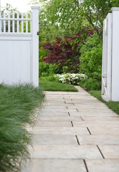 A path of staggered Cedar Lake granite pavers along one side of the house is edged simply with grasses.