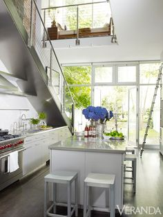 The staircase was designed to match the stainless steal countertops in this kitchen.